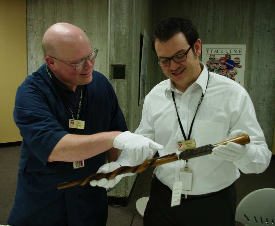 Curators examining cane carved by Confederate prisoner at Camp Chase.