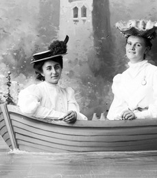 Portrait of two women in a prop boat by Albert J. Ewing.