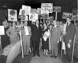 Senator Bob Taft standing next to Republican party worker Martha Wheatcraft and other supporters at a presidential campaign rally, 1950.