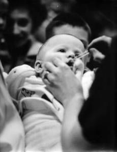 A baby being given the Type II Sabin oral polio vaccine with a dropper as part of a 1962 Youngstown immunization program; courtesy of the Rose Melnick Medical Museum, Youngstown State University; accessible online via the Ohio Memory Project.