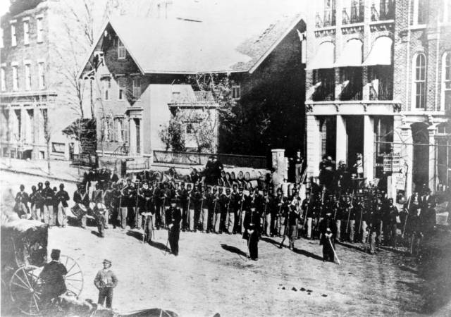 Photograph shows members of the 127th Ohio Volunteer Infantry, the first African American regiment recruited in Ohio during the Civil War. The regiment was formed in 1863, and was subsequently designated as the 5th Regiment, United States Colored Troops. The photograph was taken in Delaware, Ohio, on Sandusky Street near the Ft. Delaware Hotel.