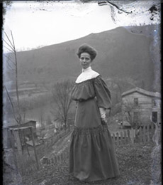 Unidentified woman photographed by Albert Ewing with a mountain landscape, circa 1896-1912.