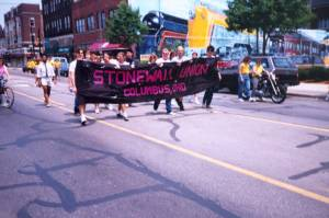 "Group carrying a ""Stonewall Union, Columbus, Ohio"" banner on High St. in the Short North area of Columbus, ca. 1993, possibly during the Gay Pride parade."