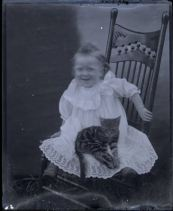 From the Albert Ewing Collection. A girl sits on a chair with her cat as her portrait is taken, likely in Southeastern Ohio.