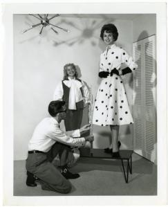 Harold Curmode adjusting hemline for Lee Ruggles.