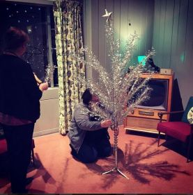 Staff prep the aluminum Christmas tree in the Lustron House.
