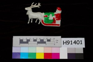 From the Ohio History Connection's collection, plastic Christmas decoration features Santa Claus in a sleigh with a single reindeer. The item is painted red and green and dates from 1955.
