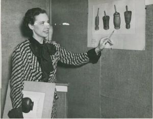 From State Archives Series 1039 AV, photograph of a woman pointing to an oil painting of vases in Cleveland, Ohio.