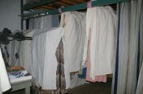 Hanging textiles are temporarily stored on rolling racks and on poles in the hanging flag rack.