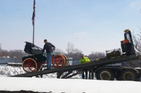Riggers carefully unload the Winton automobile from a flatbed truck.